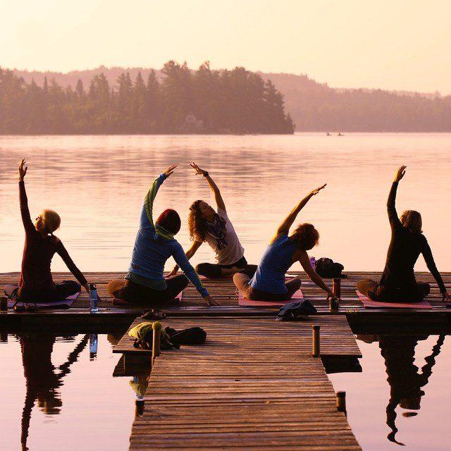 5 women doing yoga on a dock
