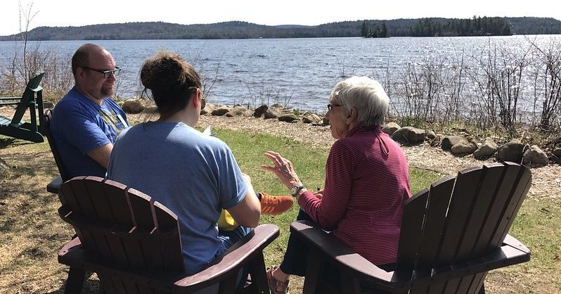 Two women and a man sitting outside in chairs chatting near a lake