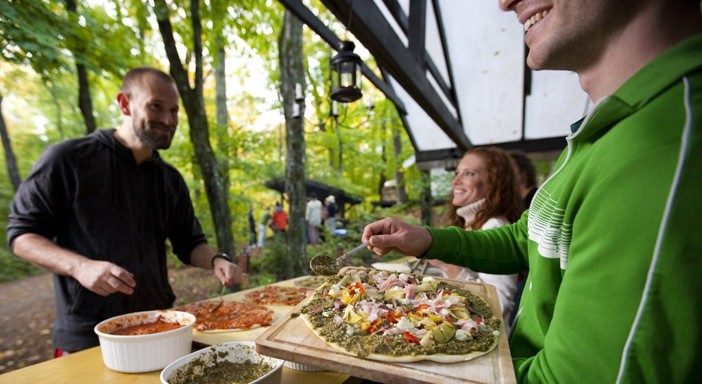 Man prepareing homemade pizza at outoor kitchen