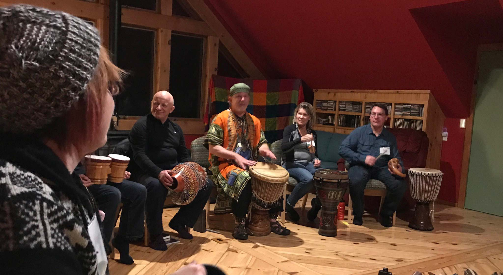 Guests participate in a drum circle with a local artist