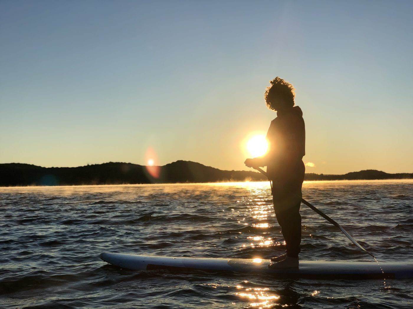 Stand up paddleboarding in the lake at sunset