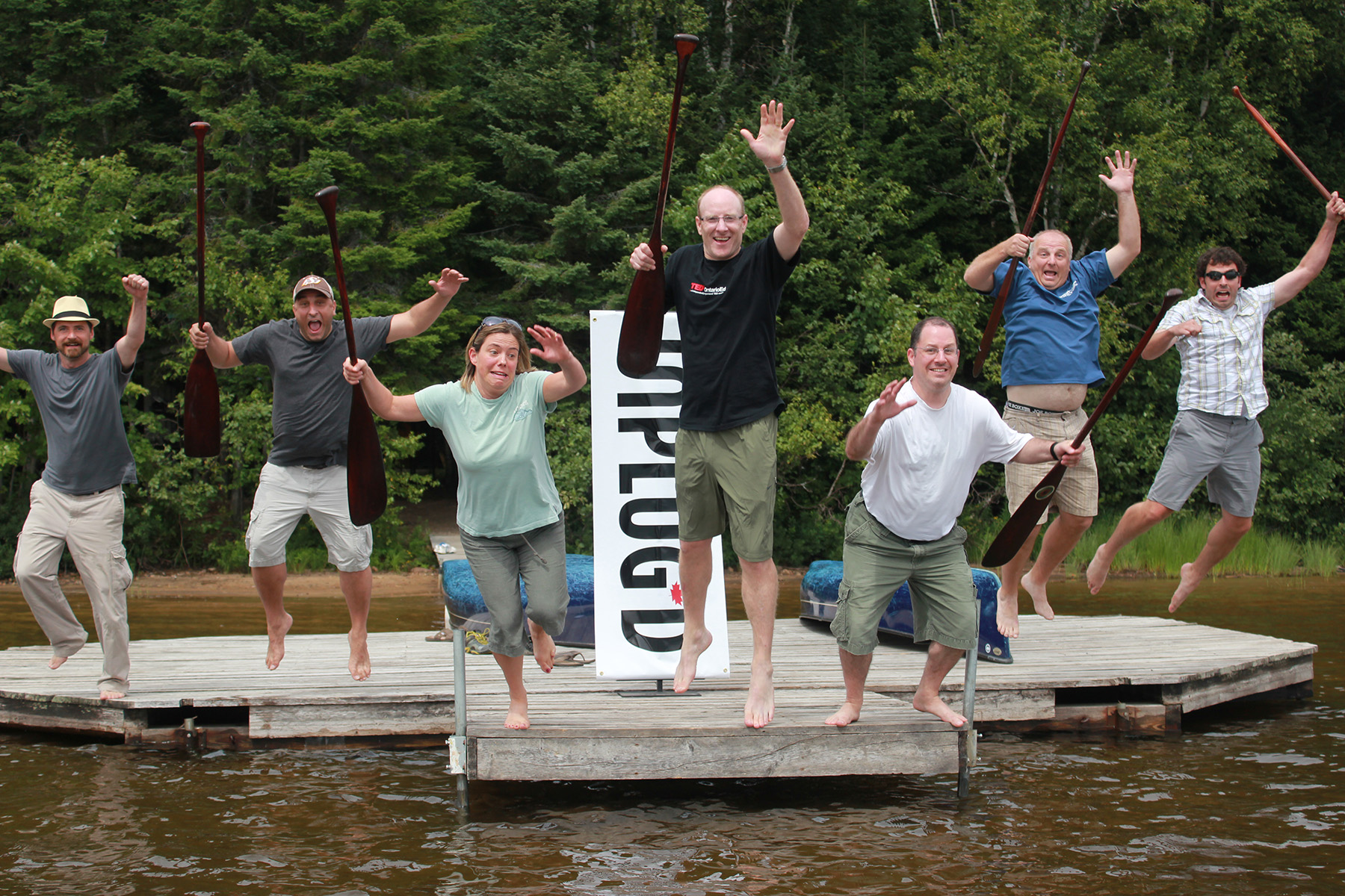 A corporate team does a creative group photo on the dock of Kawawaymog Lake