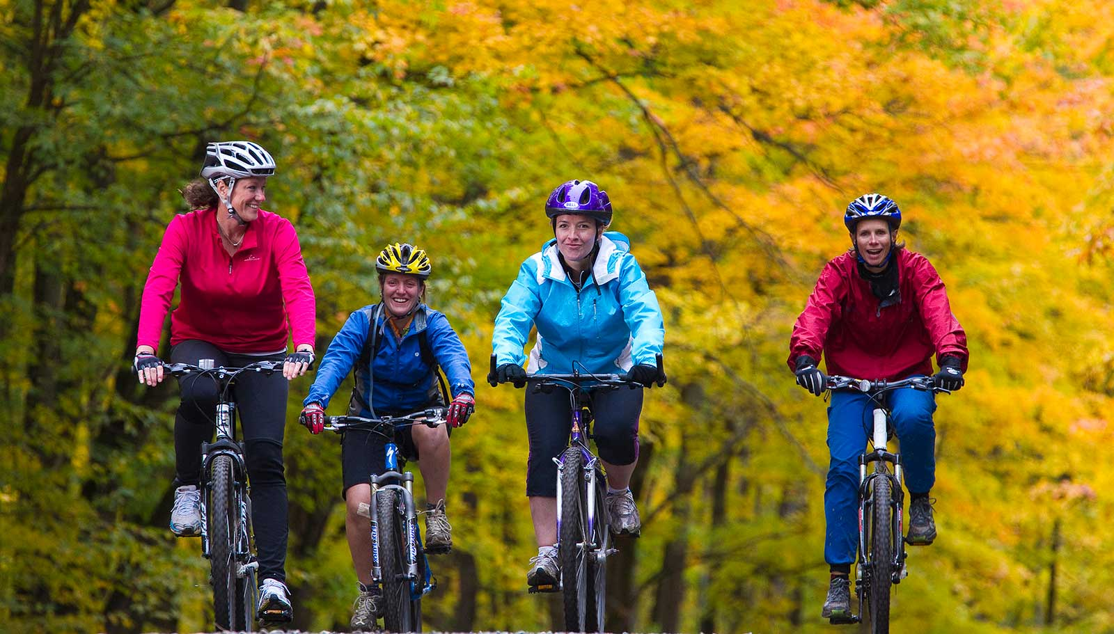 Women biking together in Algonquin Park in fall