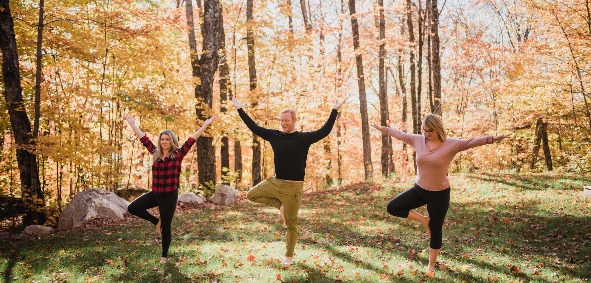Three Northern Edge Algonquin staff doing yoga in the grass