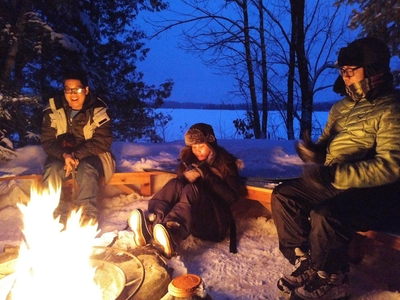 Three friends enjoying a winter campfire