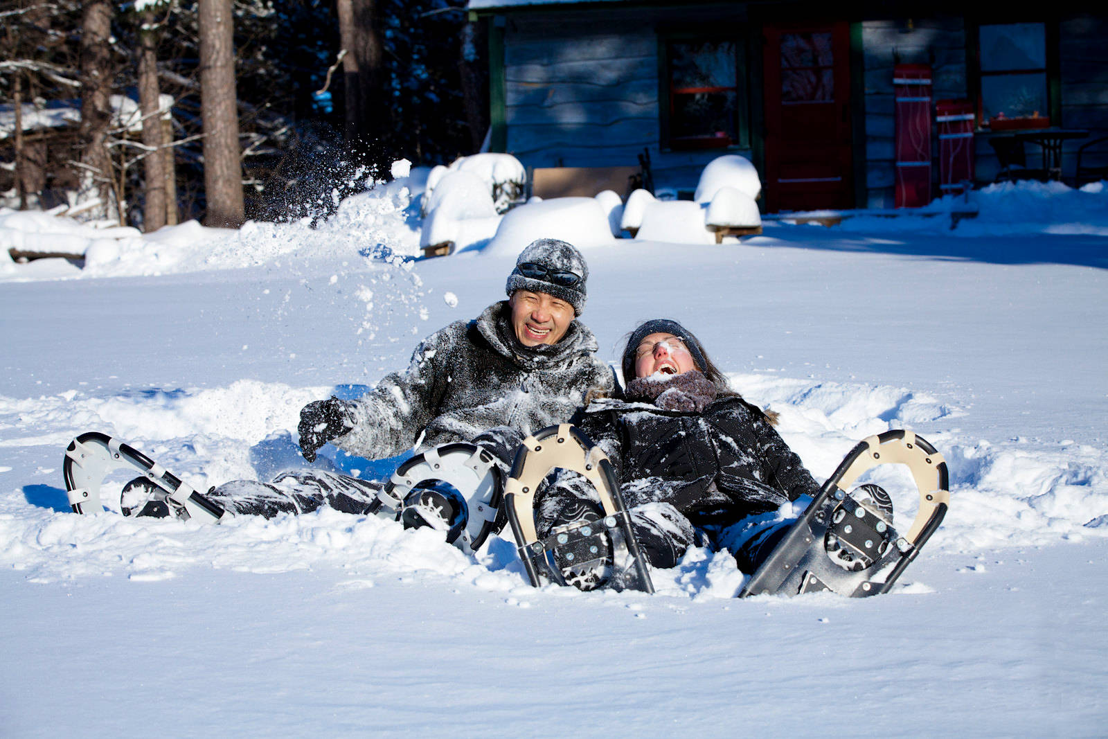 Two people laughing with snoeshoes in the winter at a retreat