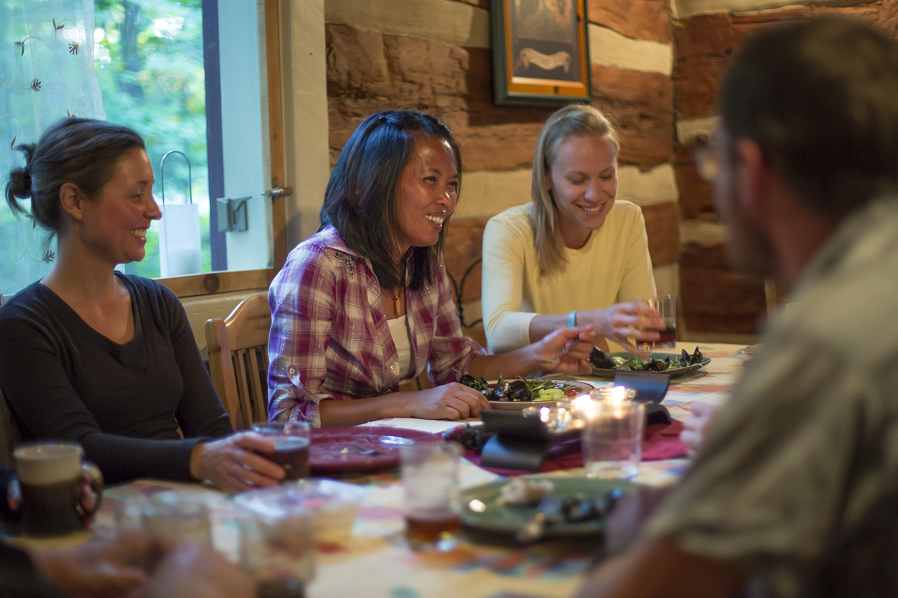 Three women sharing a meal in a rustic log cabin