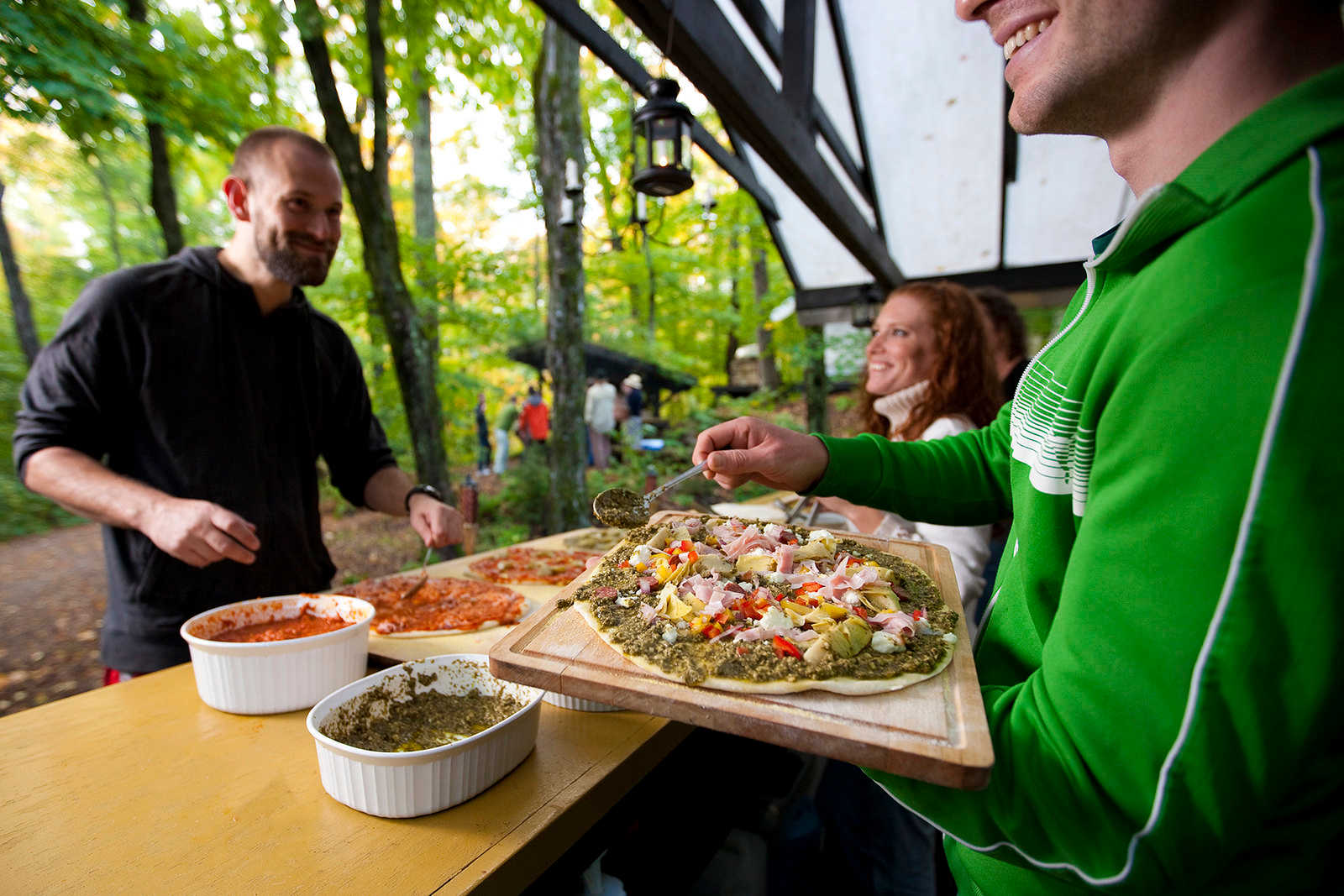 Guests making their own pizza in the oven in the forest