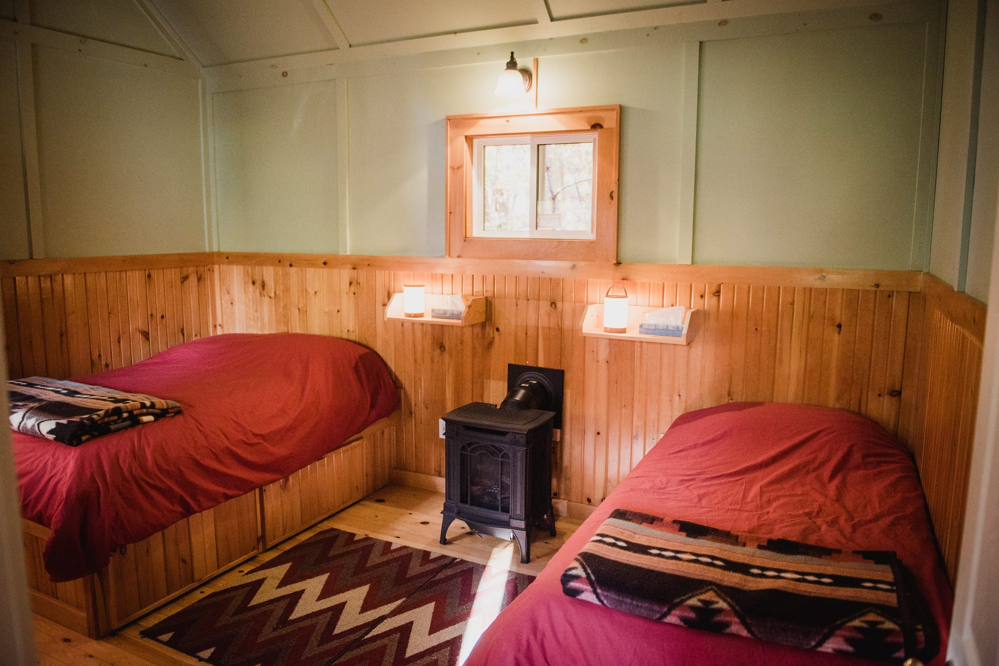 Two nicely made beds in a studio cabin