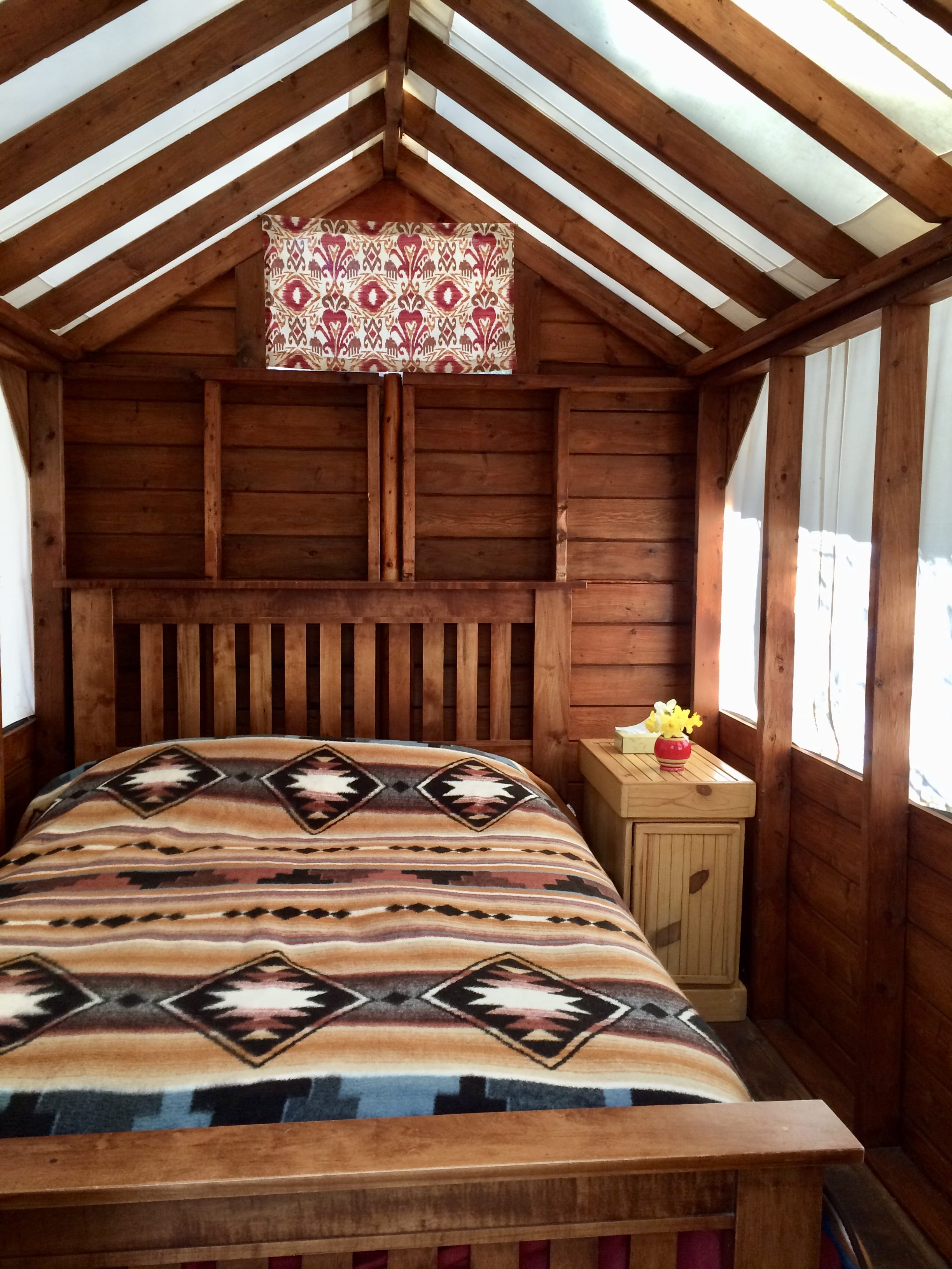 A wooden bed in a canvas cabin