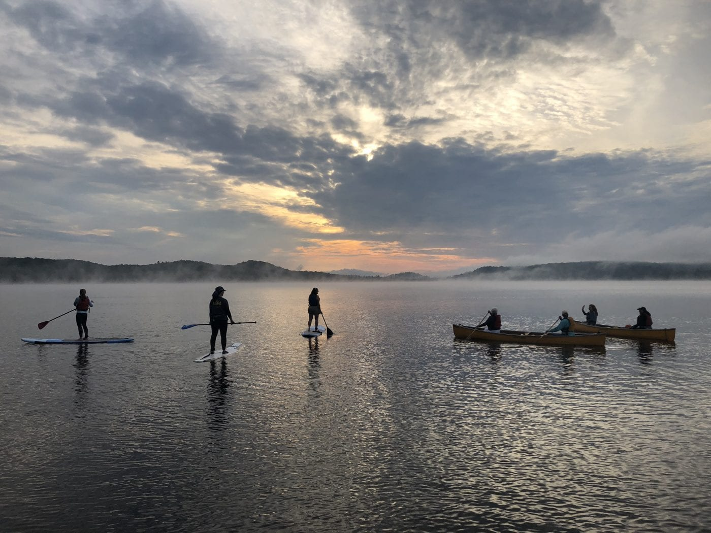A group paddling on a lake in a canoe and standup paddleboarding near Algonquin Park