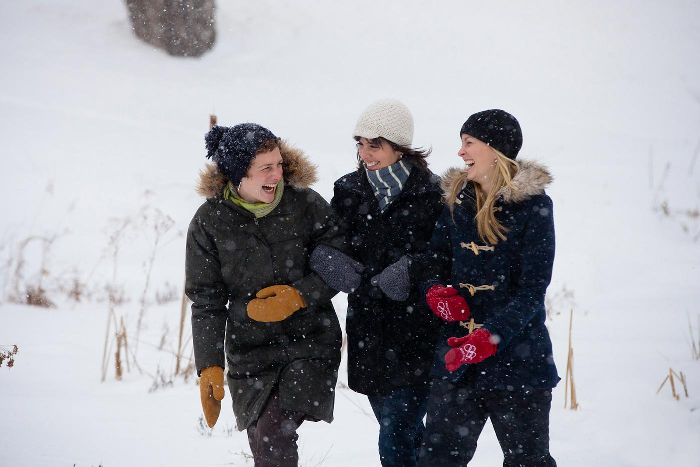 Three friends laughing in the winter snow