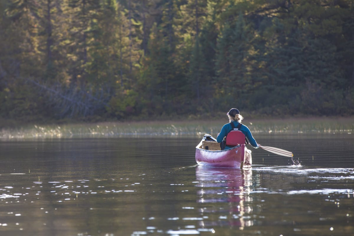 Paddling a canoe solo on a lake near Algonquin Park