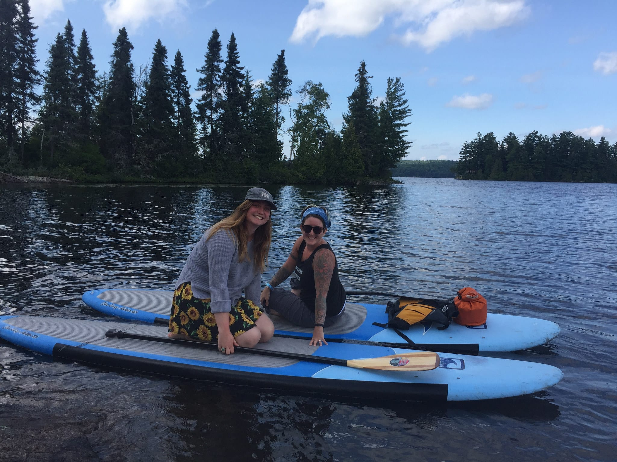 Two staff members sitting on a SUP in the lake