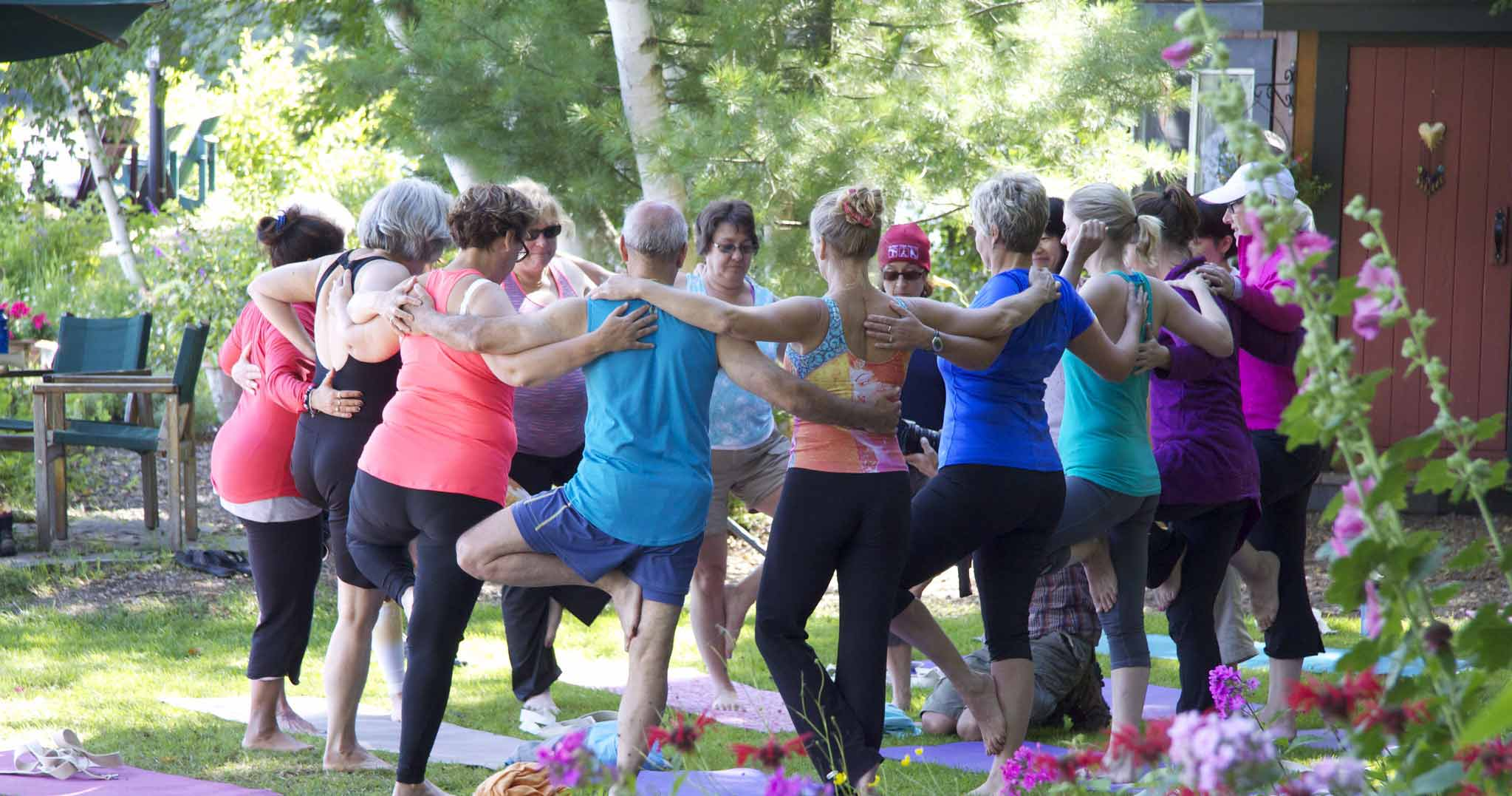 A group balancing together in a yoga pose underneath the trees