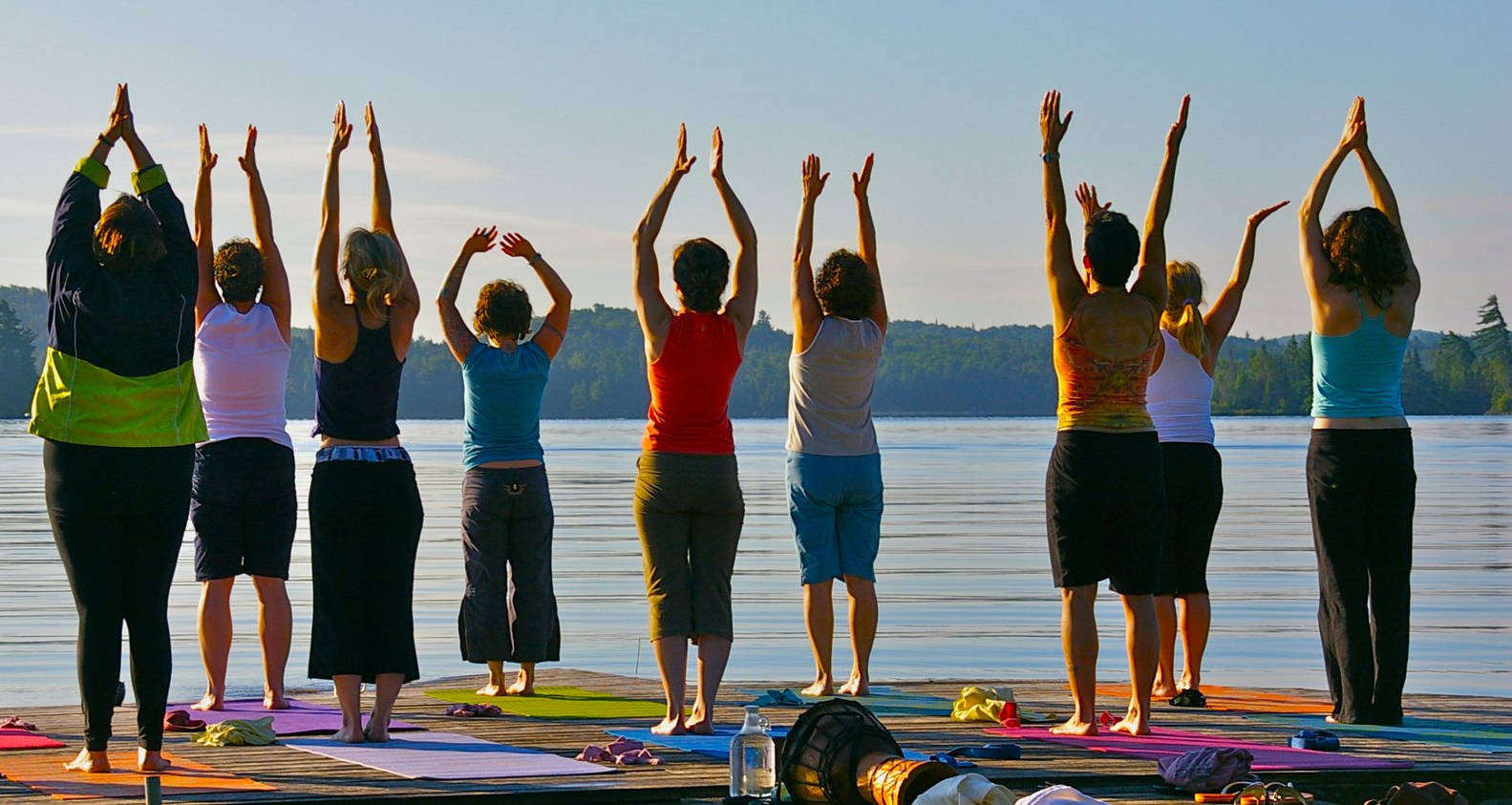 Group yoga class on the dock overlooking the lake