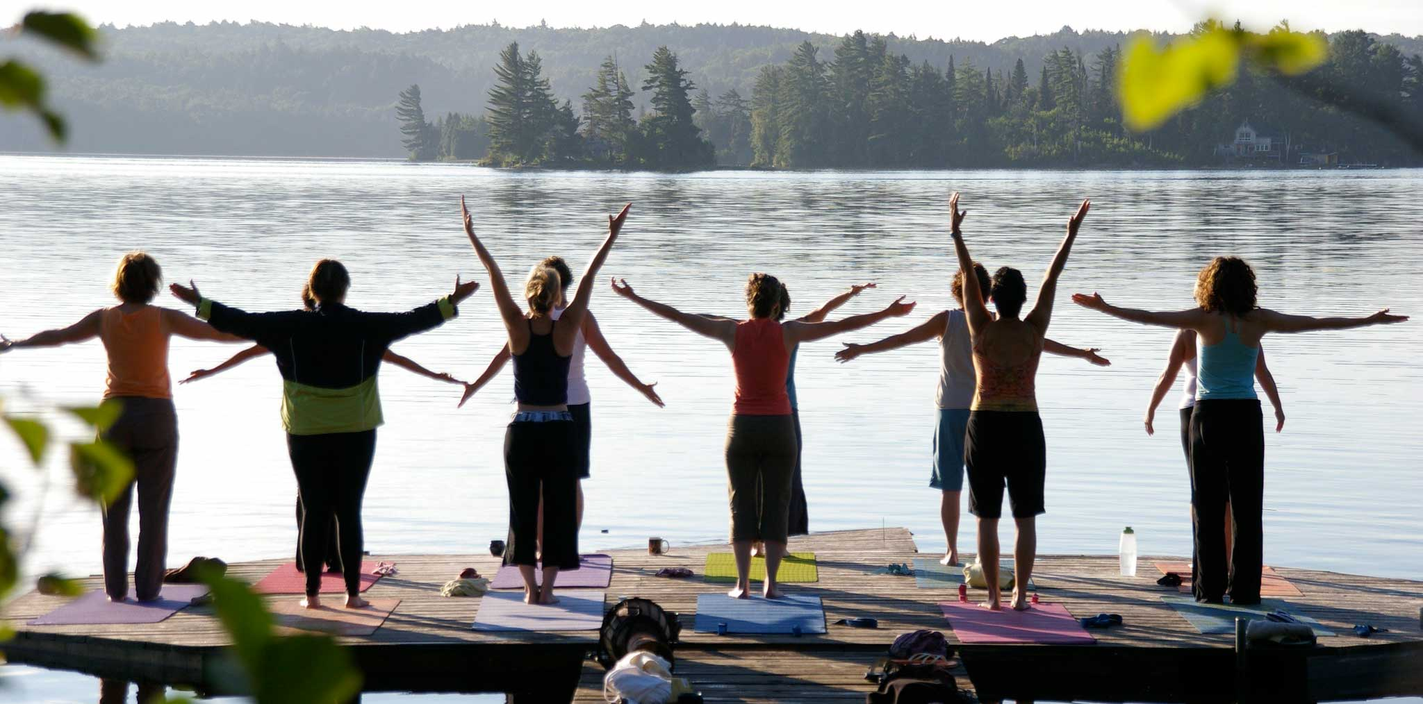 A yoga class on the dock overlooking a lake